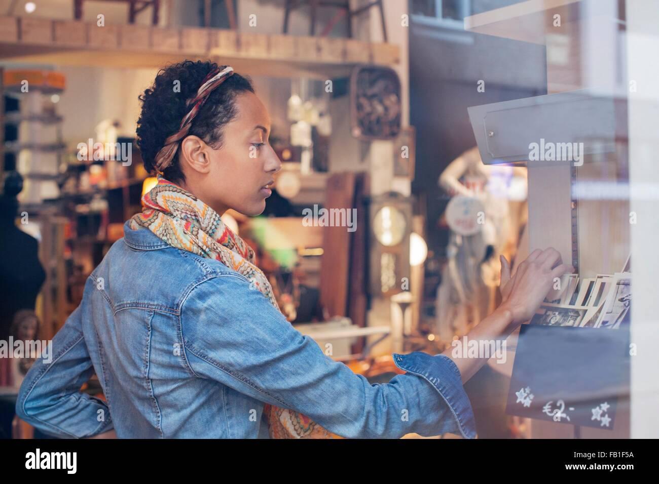 Mujer joven buscando fotografías antiguas en vintage shop Imagen De Stock
