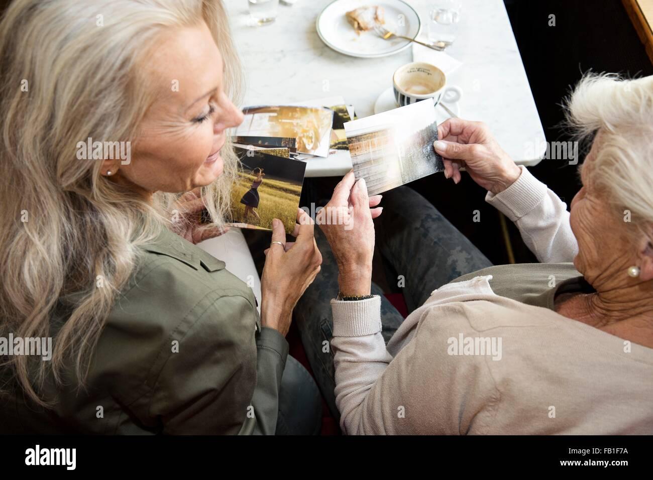 Madre e hija sentados juntos en la cafetería, mirando fotos, vista trasera Imagen De Stock