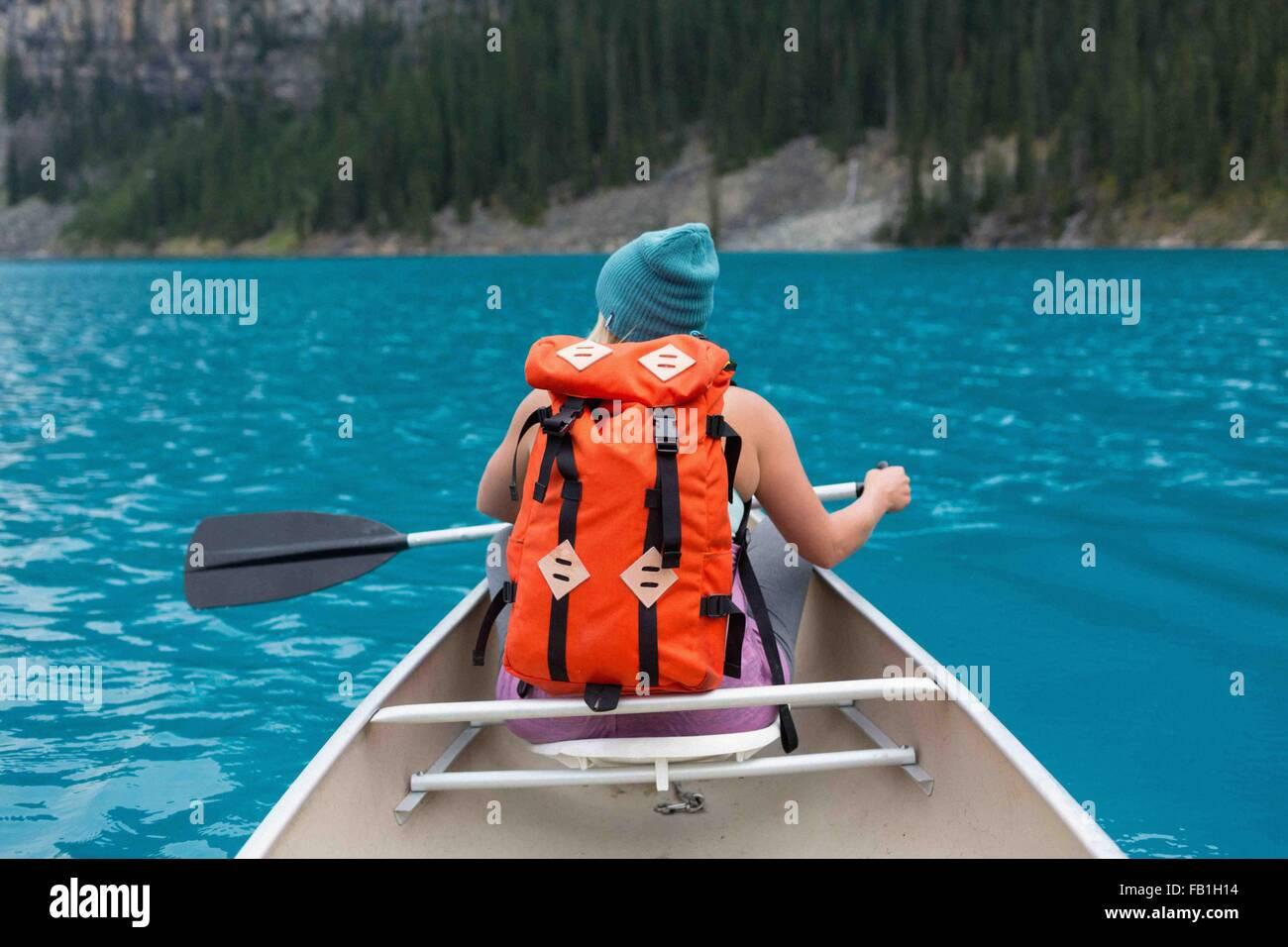 Vista trasera de mediados de mujer adulta con color naranja mochila remando en canoa, el lago Moraine, el Parque Imagen De Stock