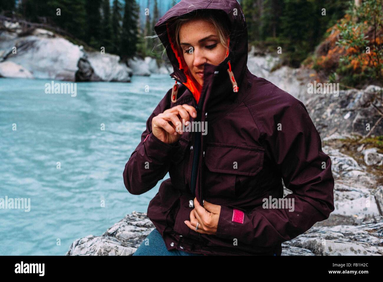 Mujer adulta media por Waters Edge surcan arriba impermeable, el lago Moraine, el Parque Nacional de Banff, Alberta, Imagen De Stock