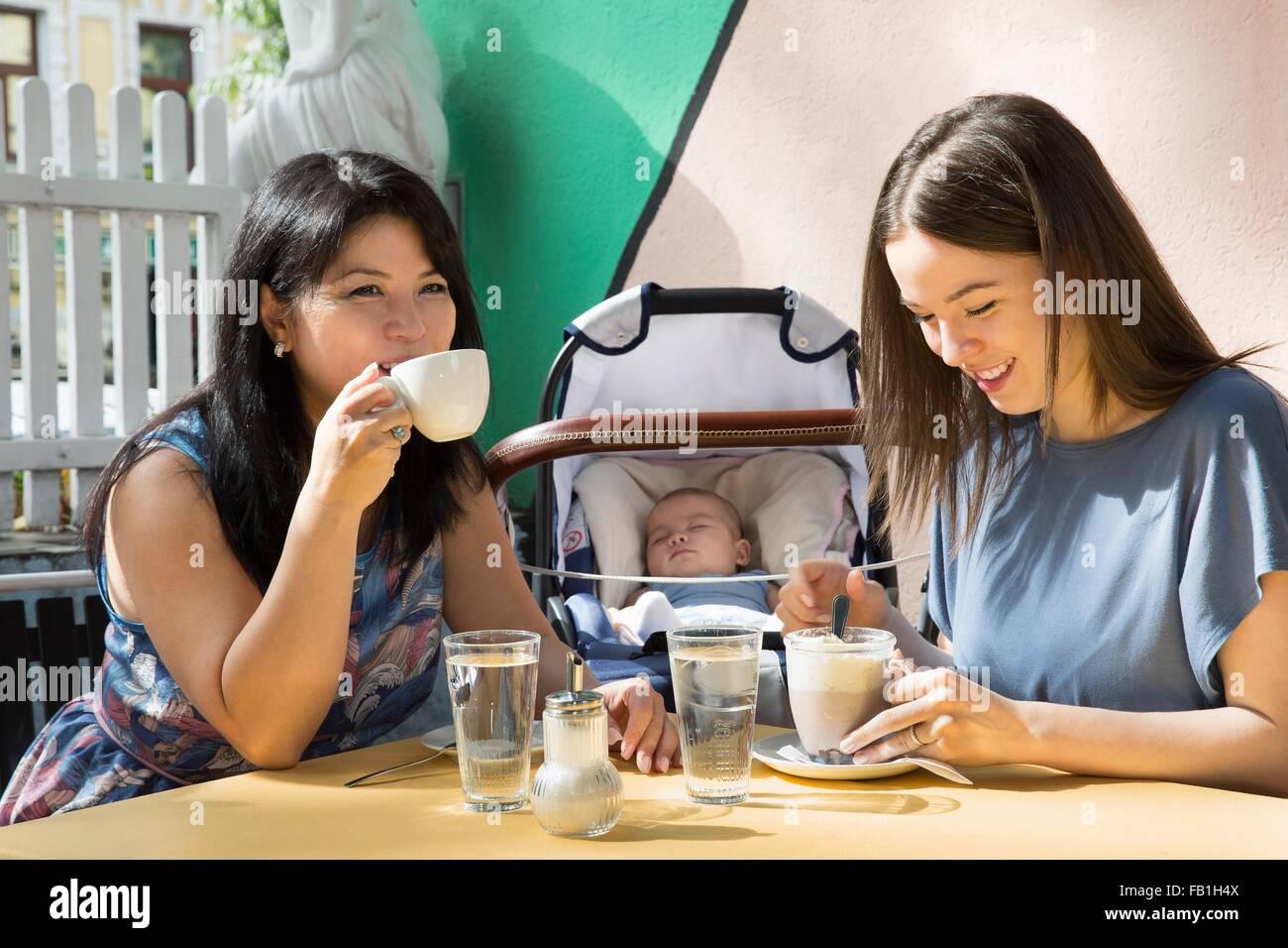 Mujer joven con la madre y la hija de beber café en la cafetería Foto de stock