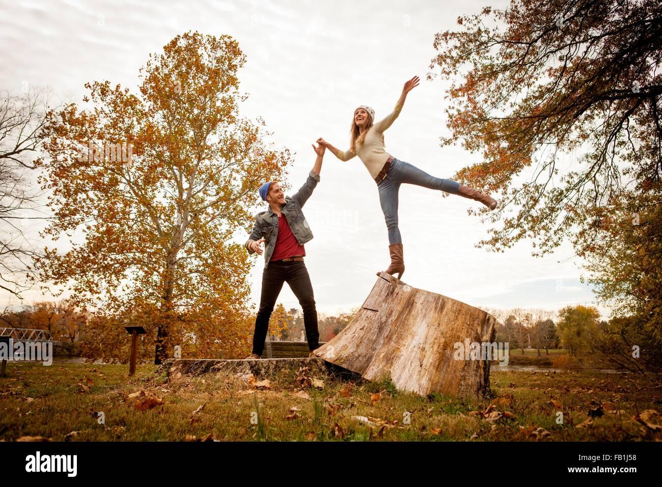 Pareja joven jugando en tocón de árbol en otoño park Foto de stock