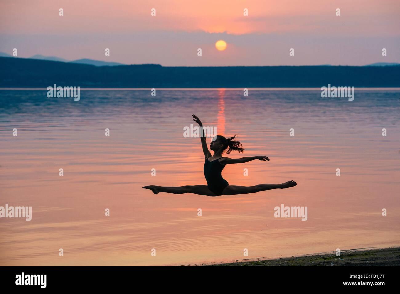 Vista lateral de la niña por mar al atardecer, saltando en el aire, brazos levantados haciendo las divisiones Imagen De Stock