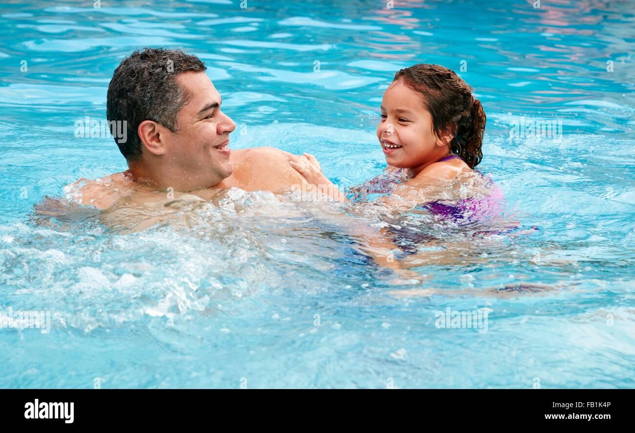 Cabeza y hombros de padre e hija en piscina sonriendo Imagen De Stock