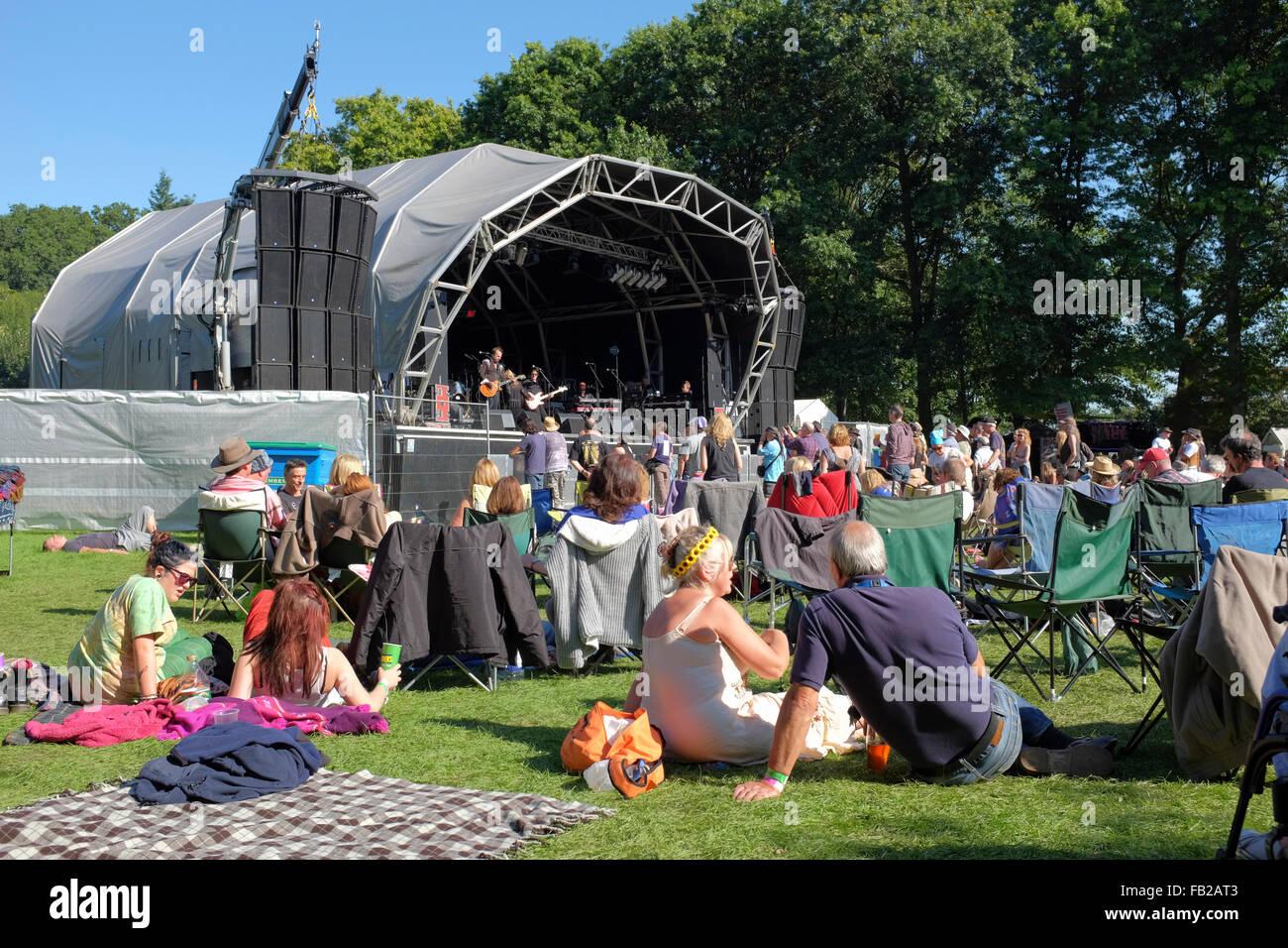 Inglaterra, Surrey, Tilford. Las personas relajarse en el sol de la tarde mientras escucha una banda, en el festival Imagen De Stock