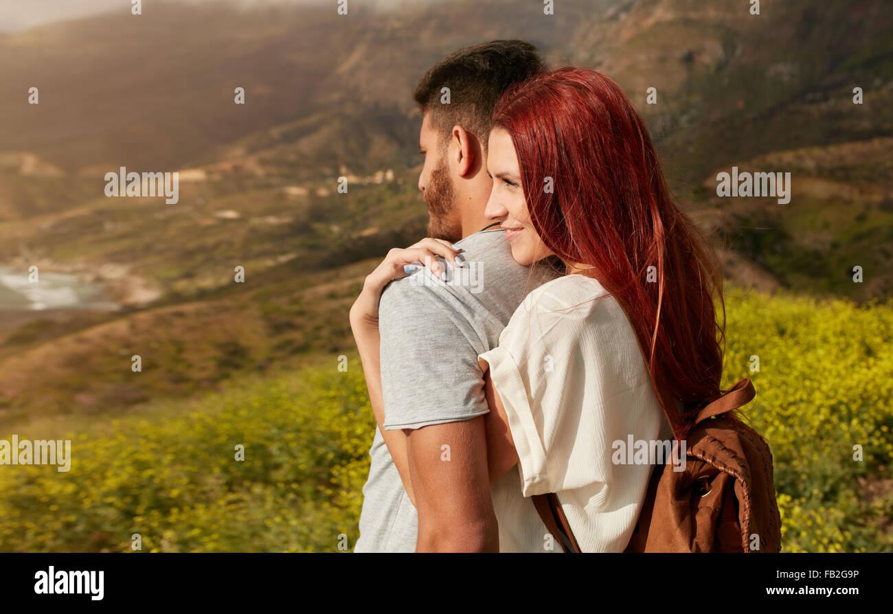 Romántica pareja joven disfruta de las vistas mientras senderismo por la montaña. Mujer joven abrazando Imagen De Stock