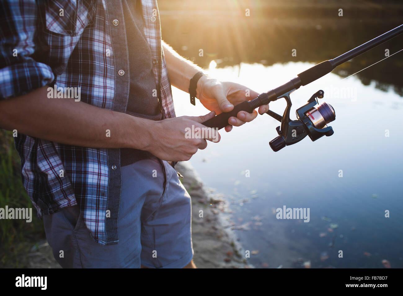 La mitad del torso del Hombre que pesca en Lakeshore en bosque Imagen De Stock