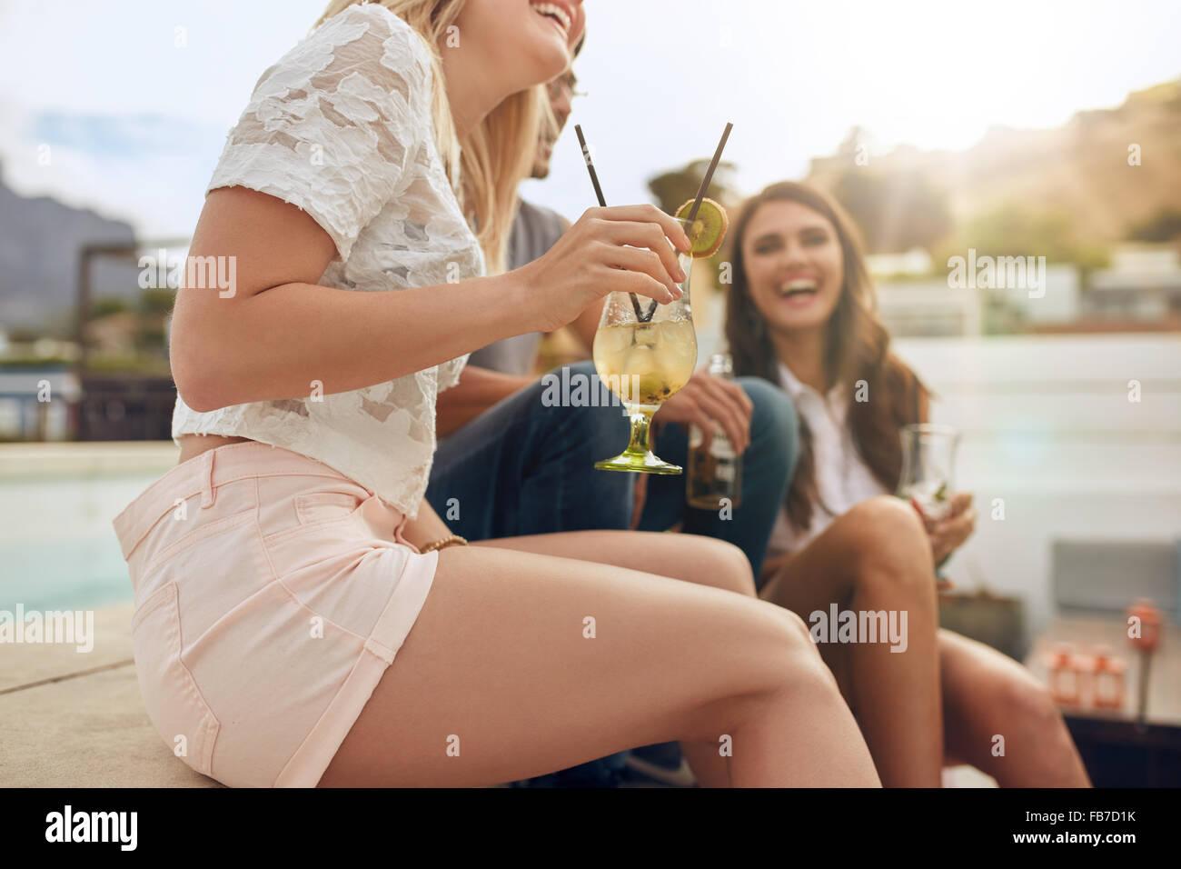 Captura recortada de jóvenes sentados junto a juntarse con bebidas. Fiesta en la azotea, con foco en vaso de Imagen De Stock