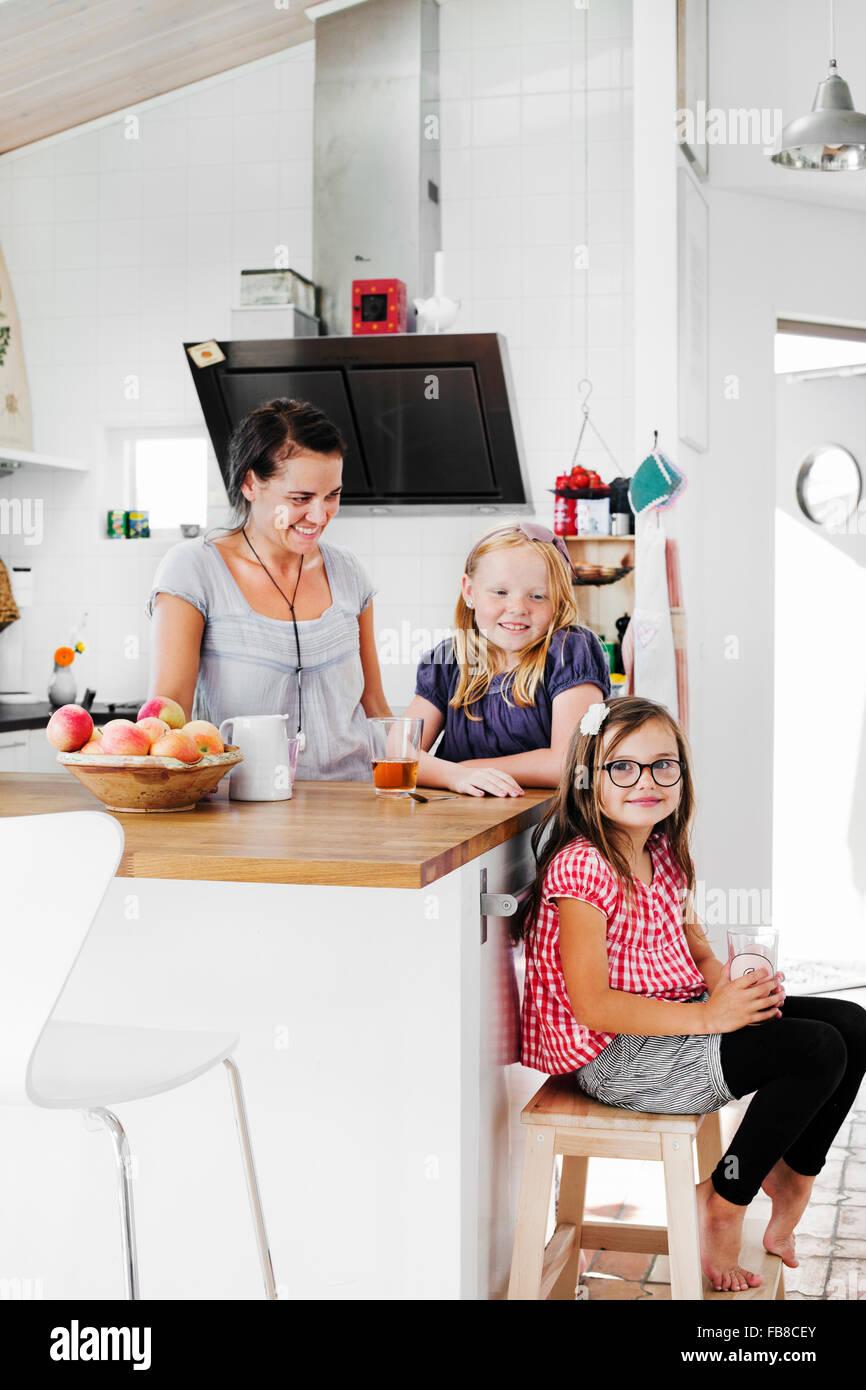 Suecia, madre y sus hijas (6-7, 8-9) sonriendo en la cocina Imagen De Stock