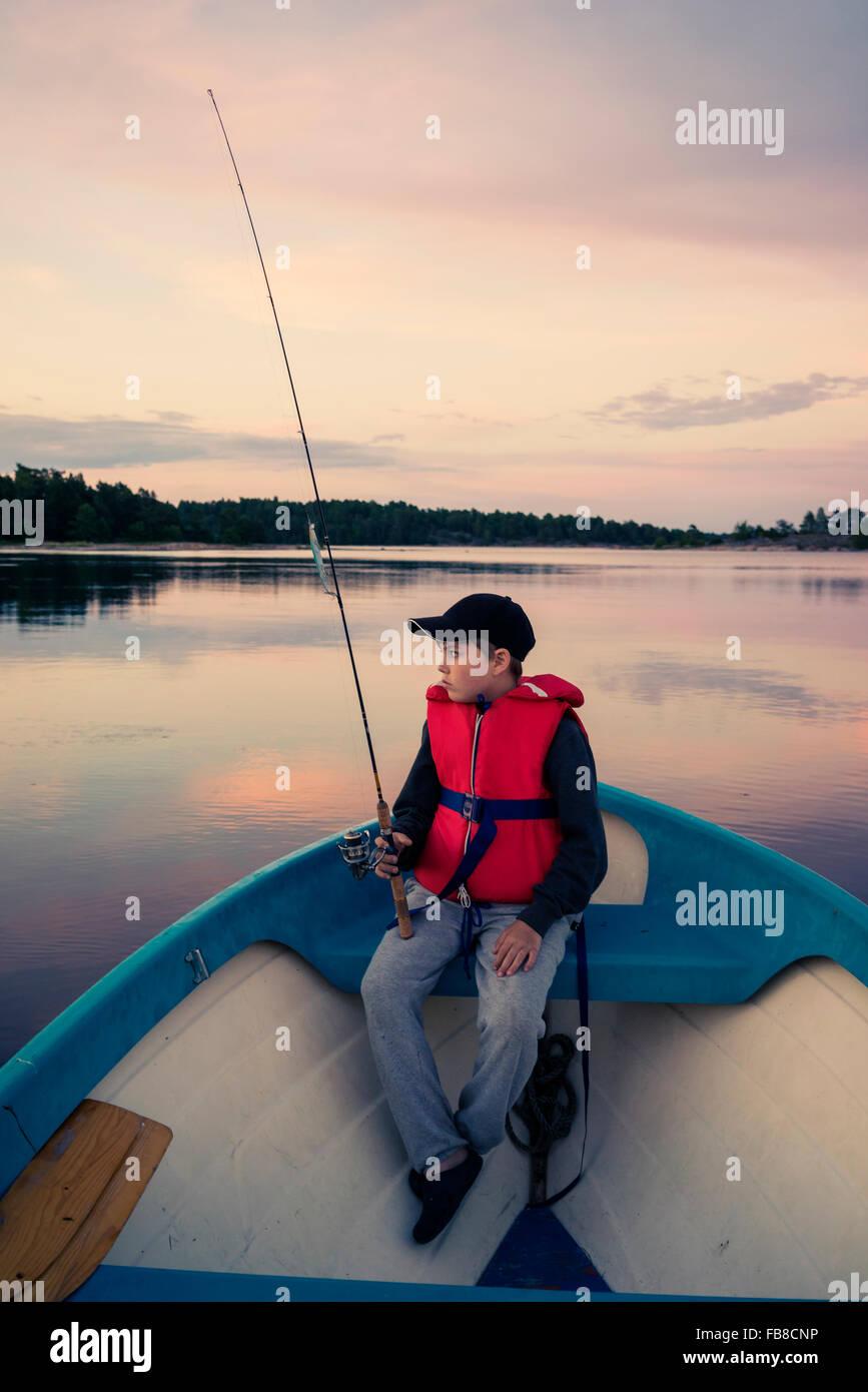 Suecia, Smaland, archipiélago Tjust Vastervik, Hasselo, Boy (10-11) en el barco de pesca con mosca en el lago Imagen De Stock
