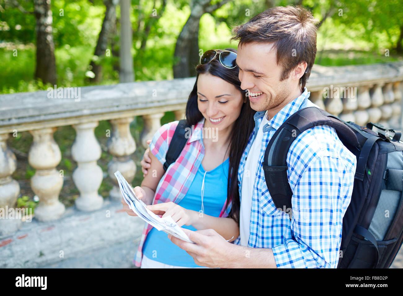Par de turistas consultar una guía de la ciudad buscando lugares en la calle Imagen De Stock