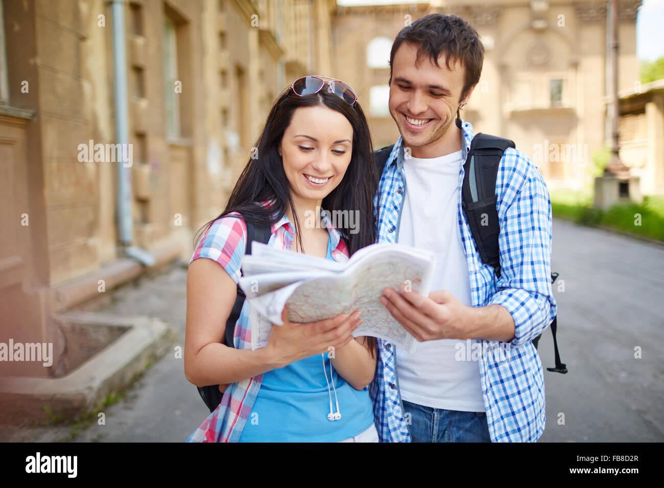 Feliz pareja de turistas de vacaciones buscando una calle en un mapa Imagen De Stock