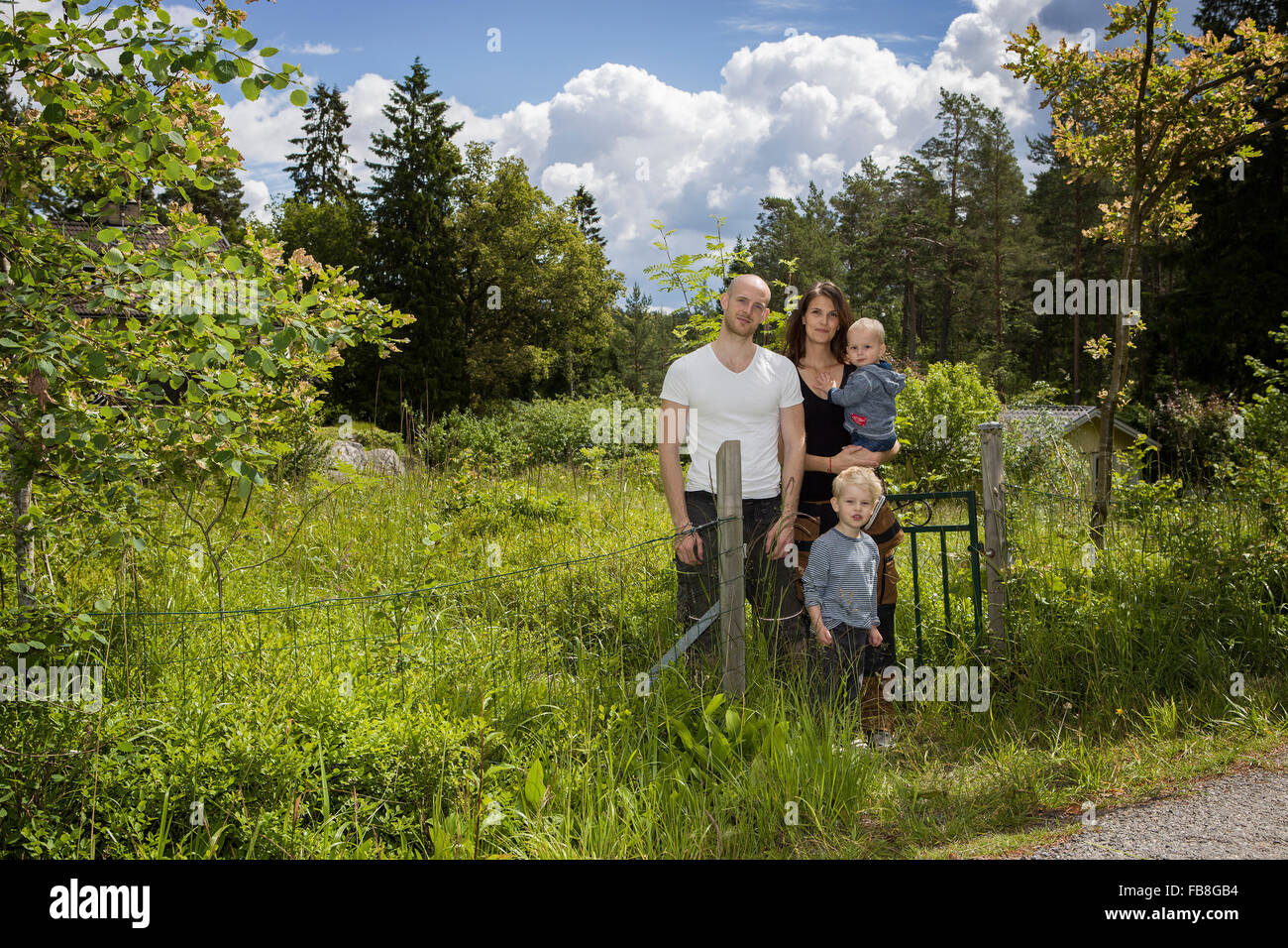Suecia, Estocolmo, Uppland, Nacka, familia con dos hijos (18-23 meses, 4-5) parado entre un exuberante follaje Foto de stock