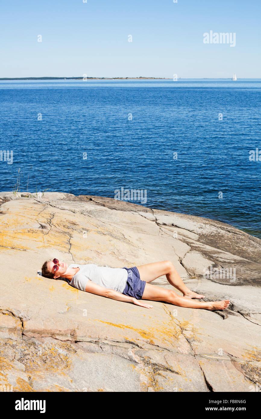 Suecia, Uppland Runmaro, Barrskar, Mujer relajante por mar Imagen De Stock