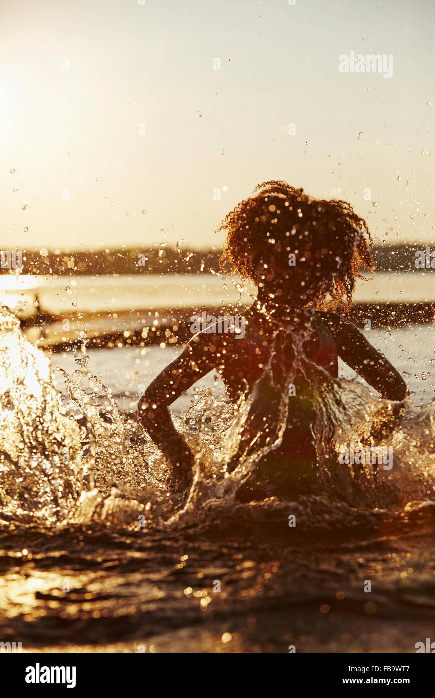 Suecia Vastra Gotaland, Skagern, Chica (6-7) salpicaduras en el lago al atardecer Imagen De Stock