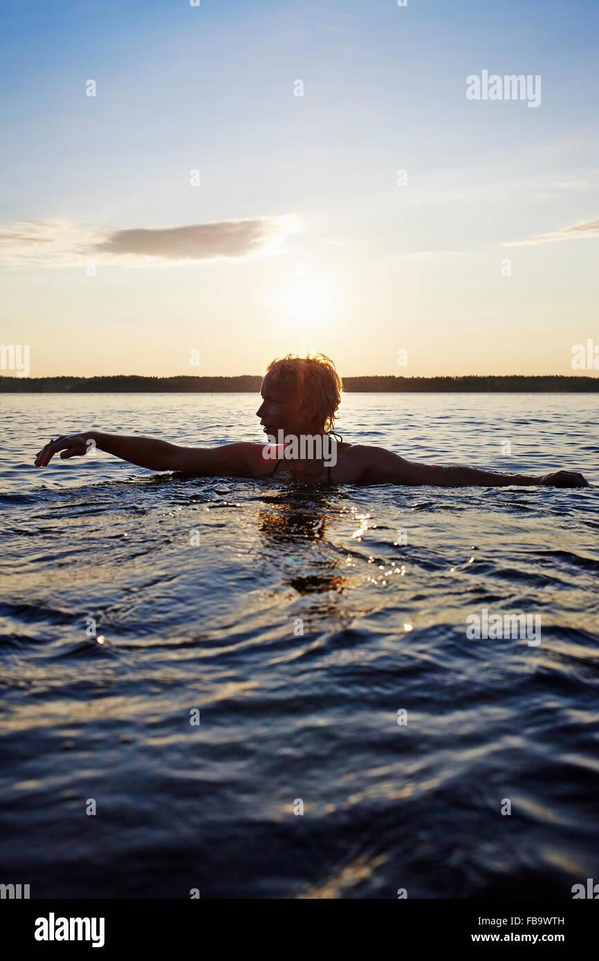 Suecia Vastra Gotaland, Skagern, Mujer nadar en el lago Imagen De Stock