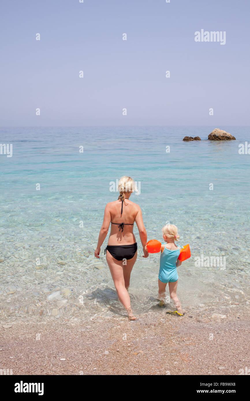 Grecia, Karpathos, la AMOPI, la mujer y la niña (6-7) caminando en el mar Foto de stock
