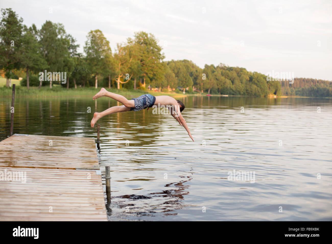 Suecia, Smaland, Braarpasjon, Boy (12-13) saltando en el lago desde el embarcadero Imagen De Stock