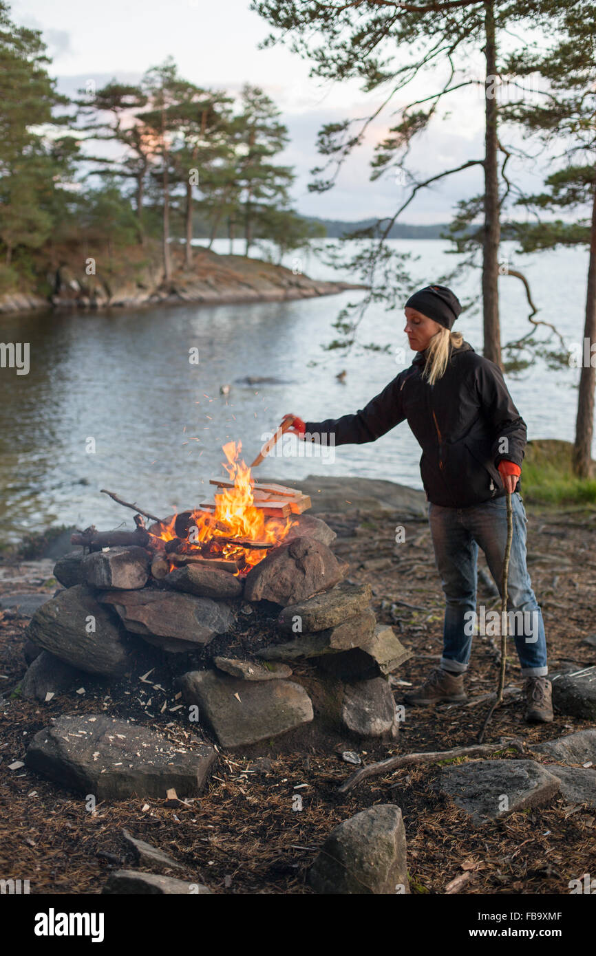 Suecia, Vastergotland, Lerum, Mujer lanzando el pedazo de madera en la hoguera por el lago al atardecer Harsjon Foto de stock