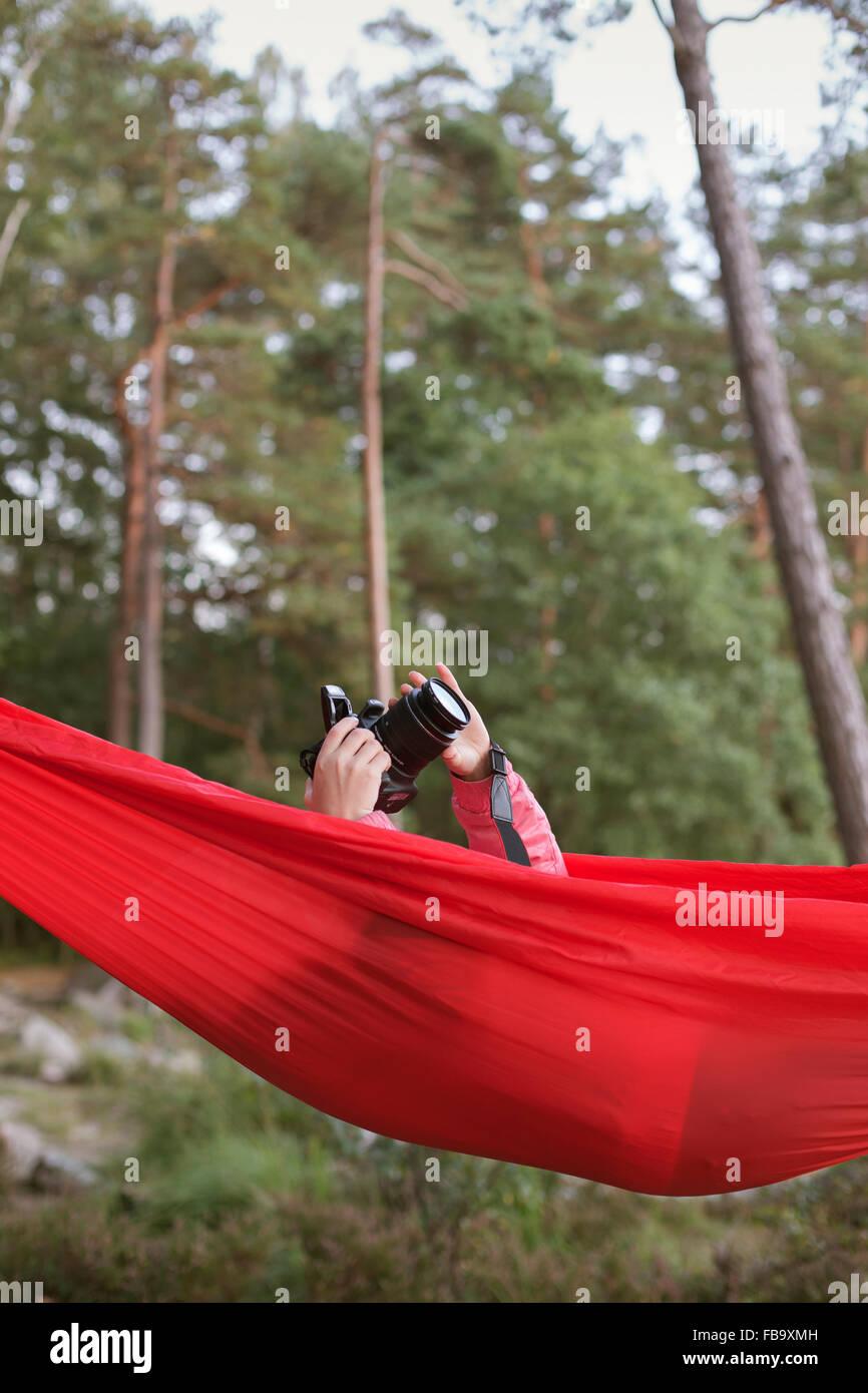 Suecia, Vastergotland, Lerum, Girl (10-11) acostado en la hamaca y tomar fotografías con la cámara Foto de stock