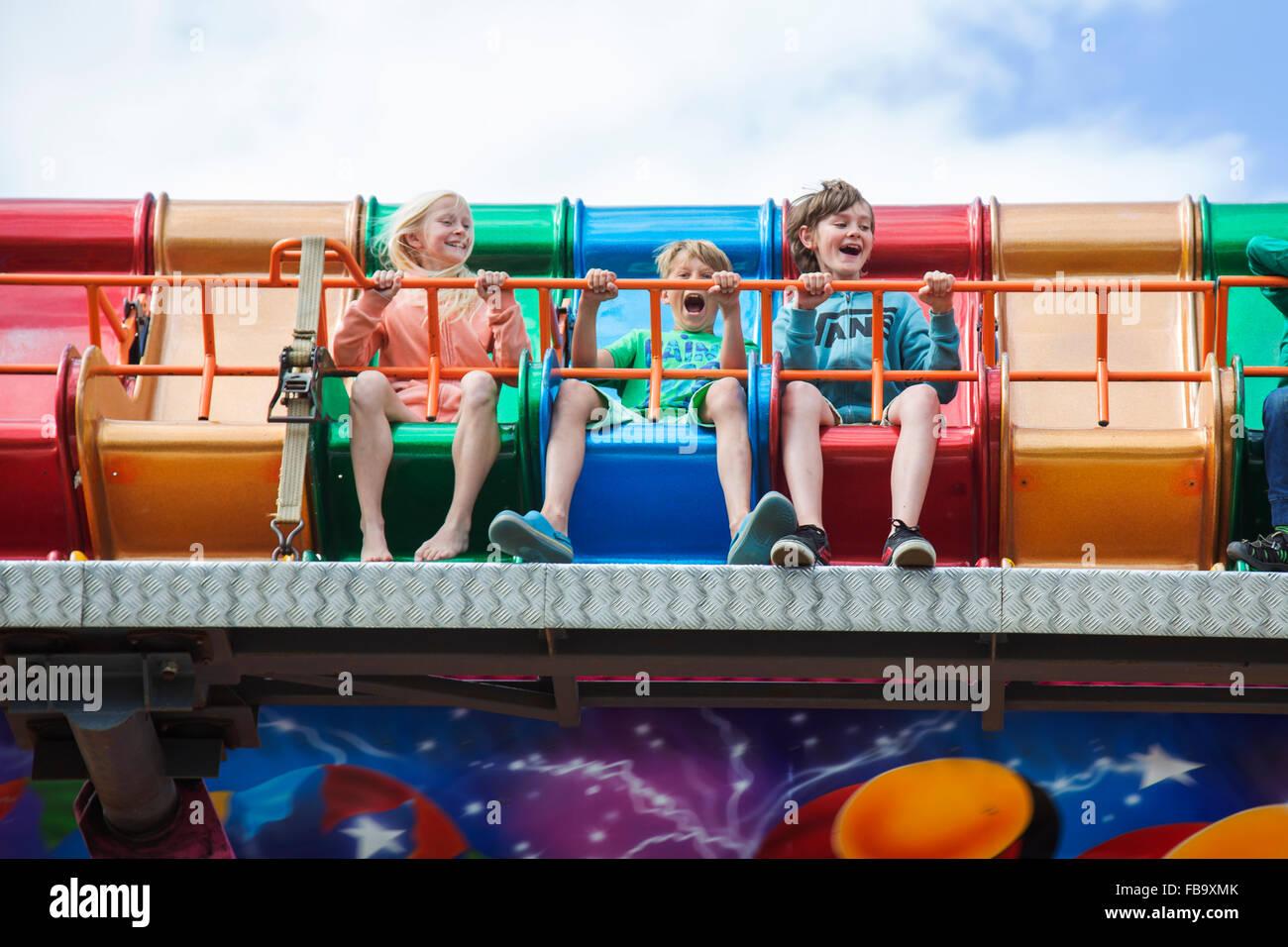 Suecia, Skane, Simrishamn, niños entusiasmados (10-11, 12-13) en el parque de diversiones Imagen De Stock