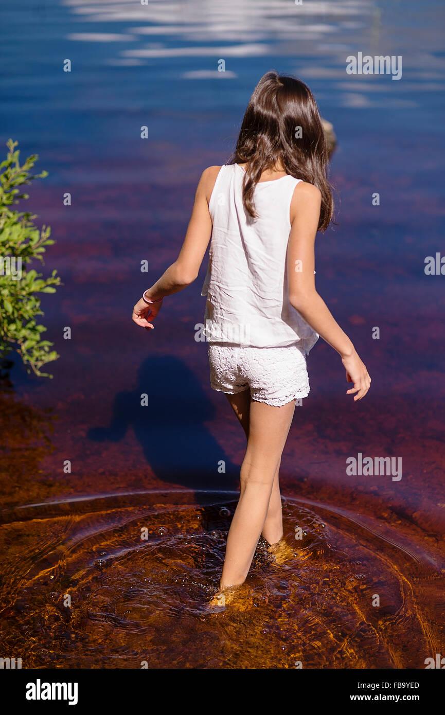 Suecia, Vastmanland, Bergslagen, Svartalven, vista trasera de chica (8-9) vadeando en el río. Imagen De Stock