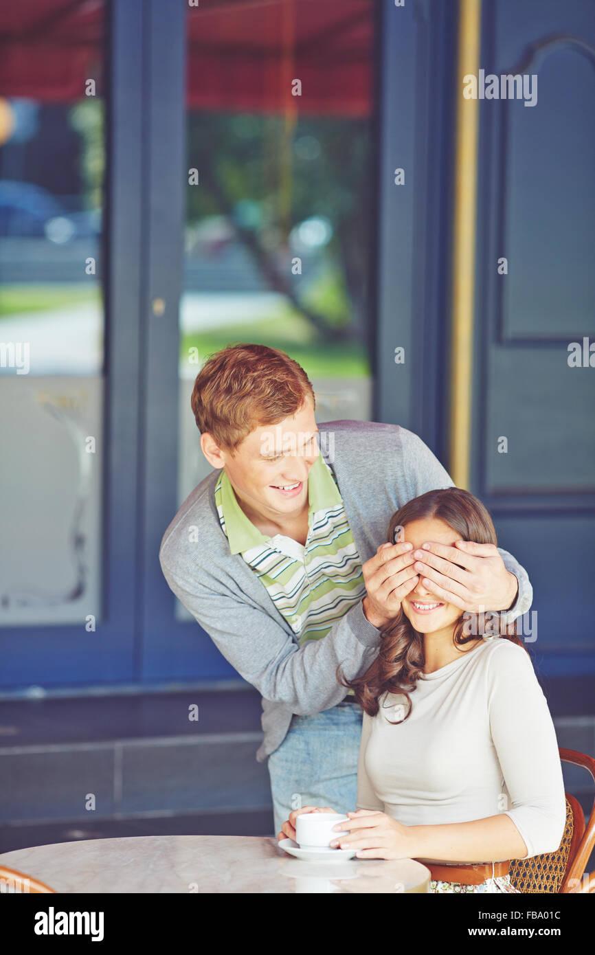 Hombre sonriente sorprender a su novia en una cafetería de la calle Imagen De Stock
