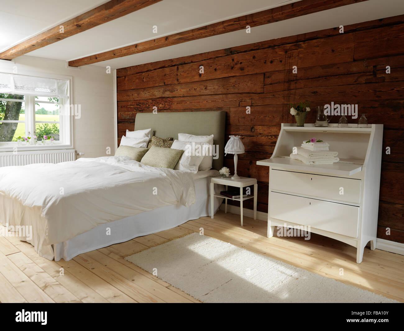 Suecia, dormitorio de estilo escandinavo con colores blanco y madera. Imagen De Stock