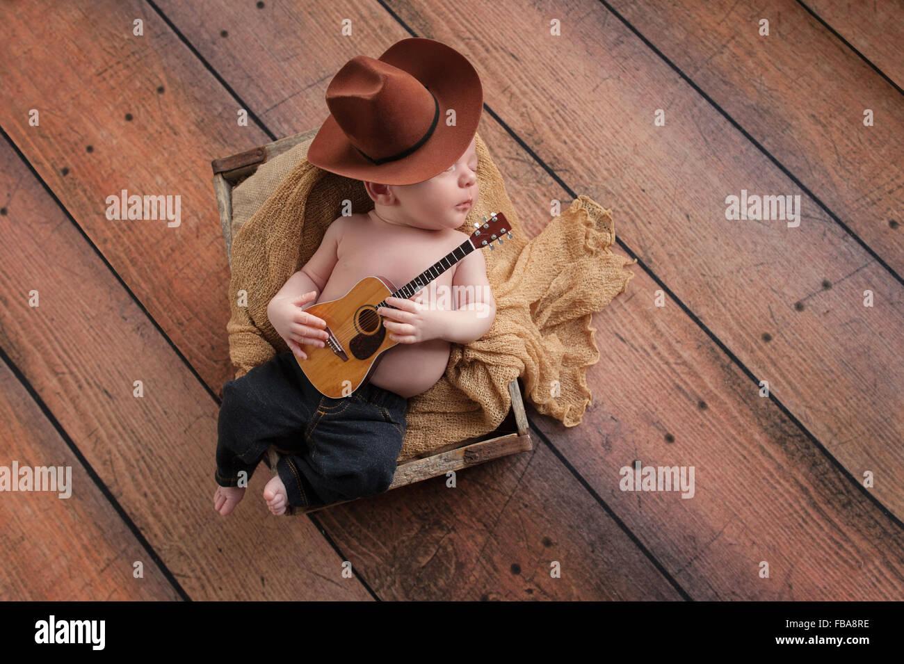 df21ff862 Un bebé de tres semanas de edad vistiendo un sombrero de vaquero y jeans y  tocando