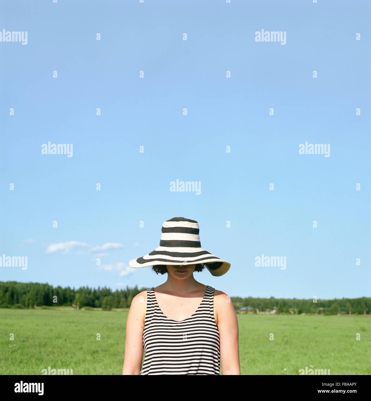 Finlandia, Uusimaa, Lapinjarvi, mujer vistiendo sombrero que cubre su rostro Imagen De Stock