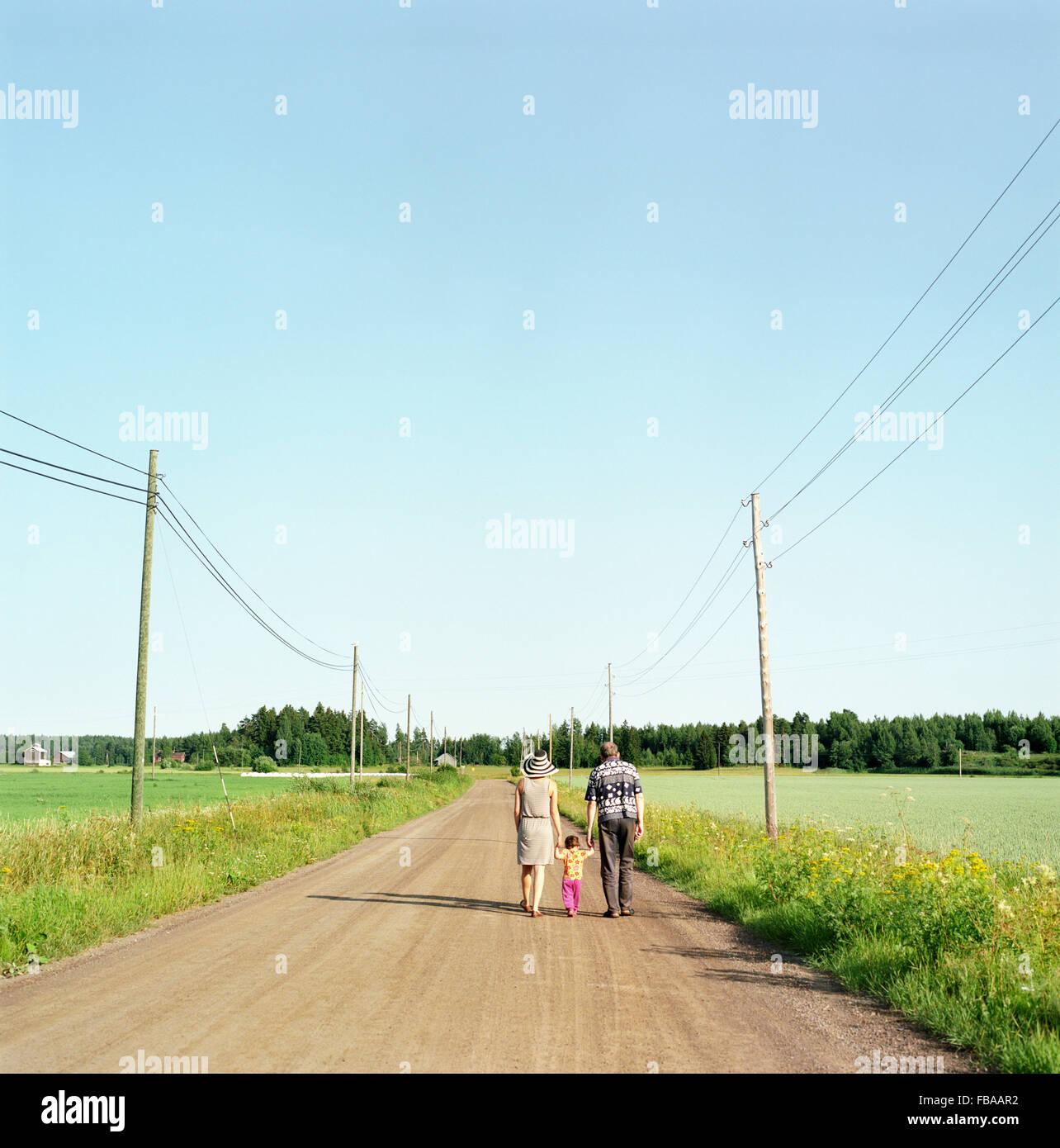 Finlandia, Uusimaa, Lapinjarvi, vista trasera de la gente con el niño (2-3) caminando por camino de tierra Imagen De Stock