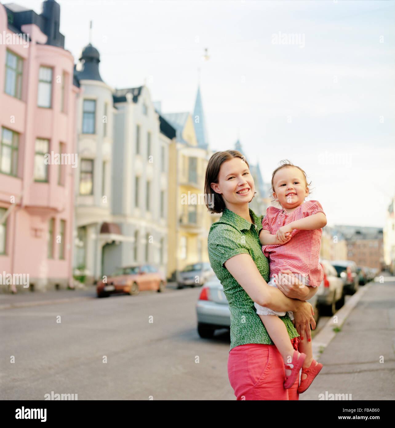 Finlandia, Helsinki, Uusimaa, retrato de la madre sosteniendo hija (2-3) en la calle Imagen De Stock