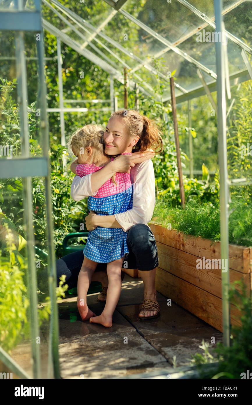 Finlandia, Heinola, Paijat-Hame, Mujer abrazando chica (4-5) en el invernadero Imagen De Stock
