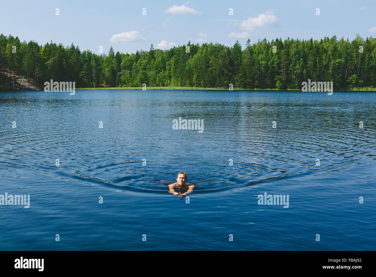 Finlandia, Uusimaa, Espoo, Lago Kvarntrask, joven nadar en el lago Imagen De Stock