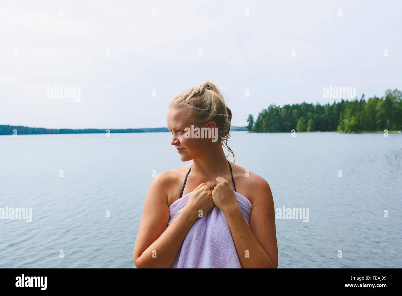 Finlandia, Pirkanmaa, Salmentaka, Lago Palkanevesi, Mujer envuelta en una toalla en el lago Imagen De Stock