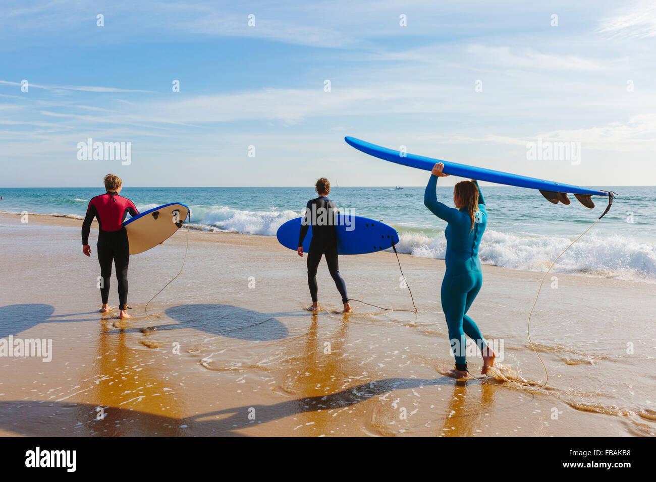 Portugal, Lisboa, tres personas llevar tablas de surf en la playa Imagen De Stock
