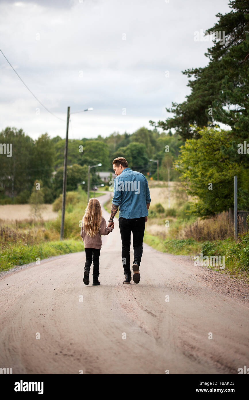 Finlandia, Uusimaa, Raasepori, Karjaa, Padre caminando con su hija (6-7) a lo largo de country road Foto de stock