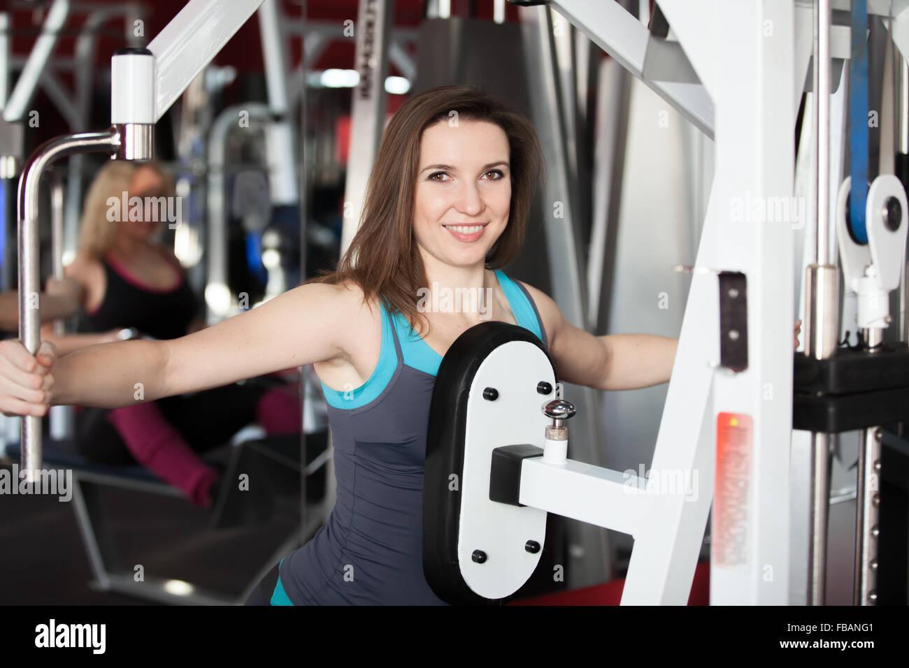 Chica sonriente en ropa deportiva hace ejercicios para brazos y hombros en aparatos de entrenamiento en el gimnasio Imagen De Stock