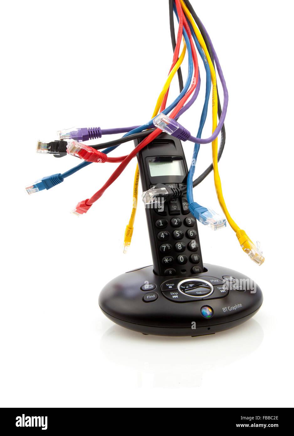 Teléfono inalámbrico negro con cables CAT 5 y cuna aislado sobre fondo blanco. Imagen De Stock