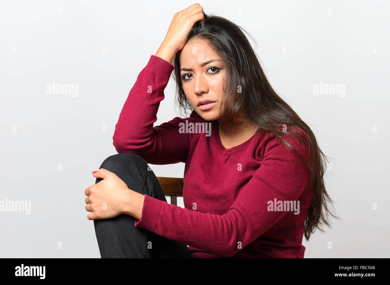 Pisado preocupado joven sentada abrazando su rodilla mirando a la cámara con una grave expresión desanimados Imagen De Stock