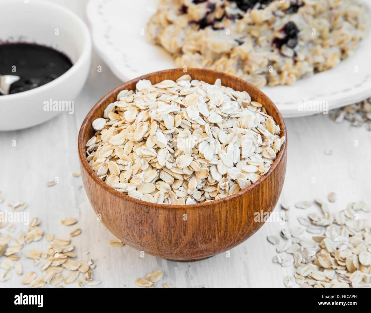 La harina de avena en un recipiente de madera y gachas en el fondo Foto de stock