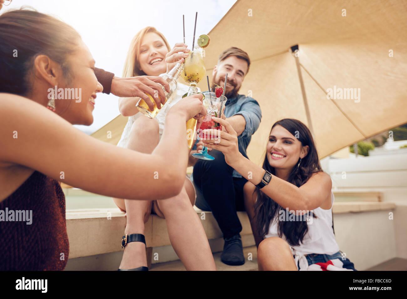 Grupo de jóvenes felices animando con cócteles y sonriente mientras la fiesta juntos en la azotea. Jóvenes Imagen De Stock