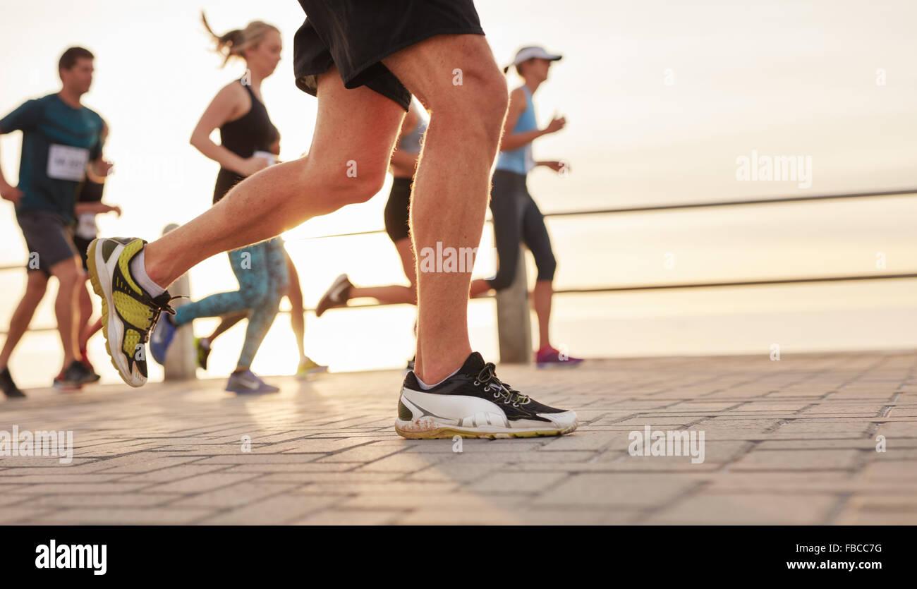 Closeup retrato de gente corriendo en carretera por el mar con el foco en los pies de hombres runner. Imagen De Stock