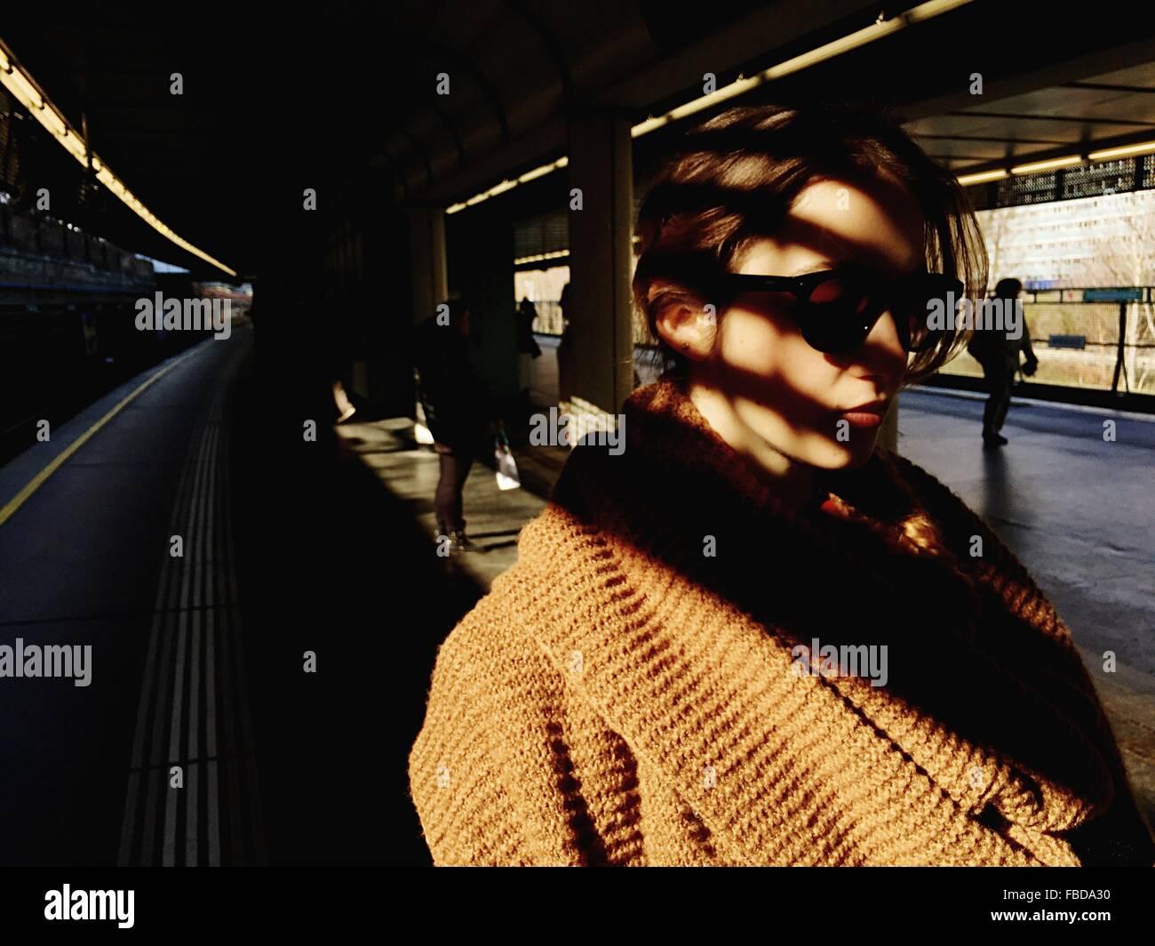Primer plano de la mujer en gafas de sol de pie sobre la plataforma de la estación de ferrocarril Imagen De Stock