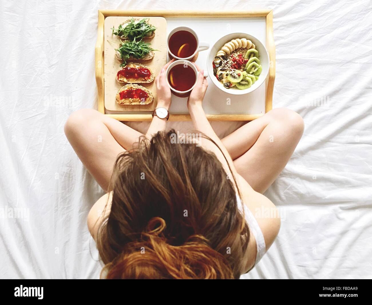 Directamente encima de foto de mujer desayunando en la cama Imagen De Stock