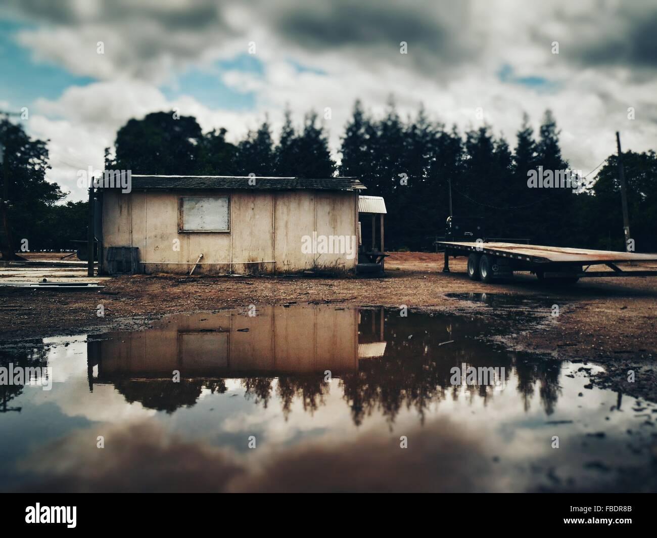 Reflejo de la estructura construida y árboles en el agua Imagen De Stock
