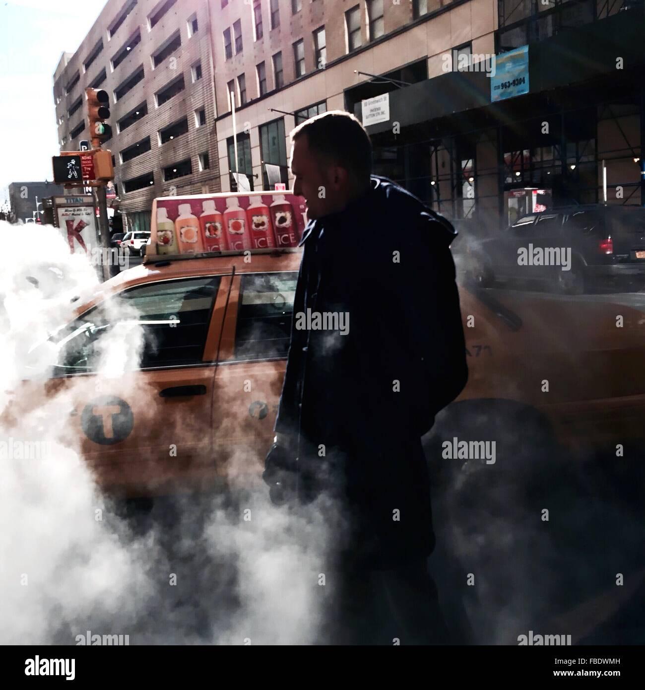 Mitad hombre adulto rodeado por el humo mientras está de pie contra el coche en la calle Foto de stock
