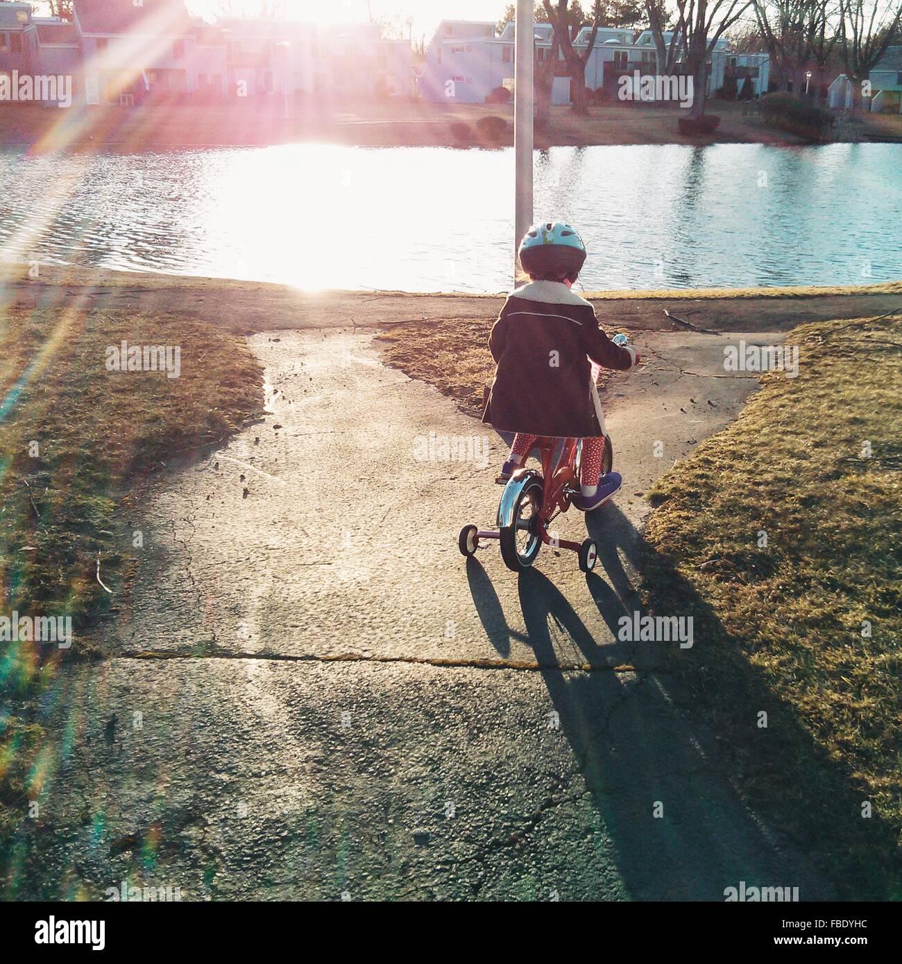 Un alto ángulo de vista de chica en bicicleta por el lago Imagen De Stock