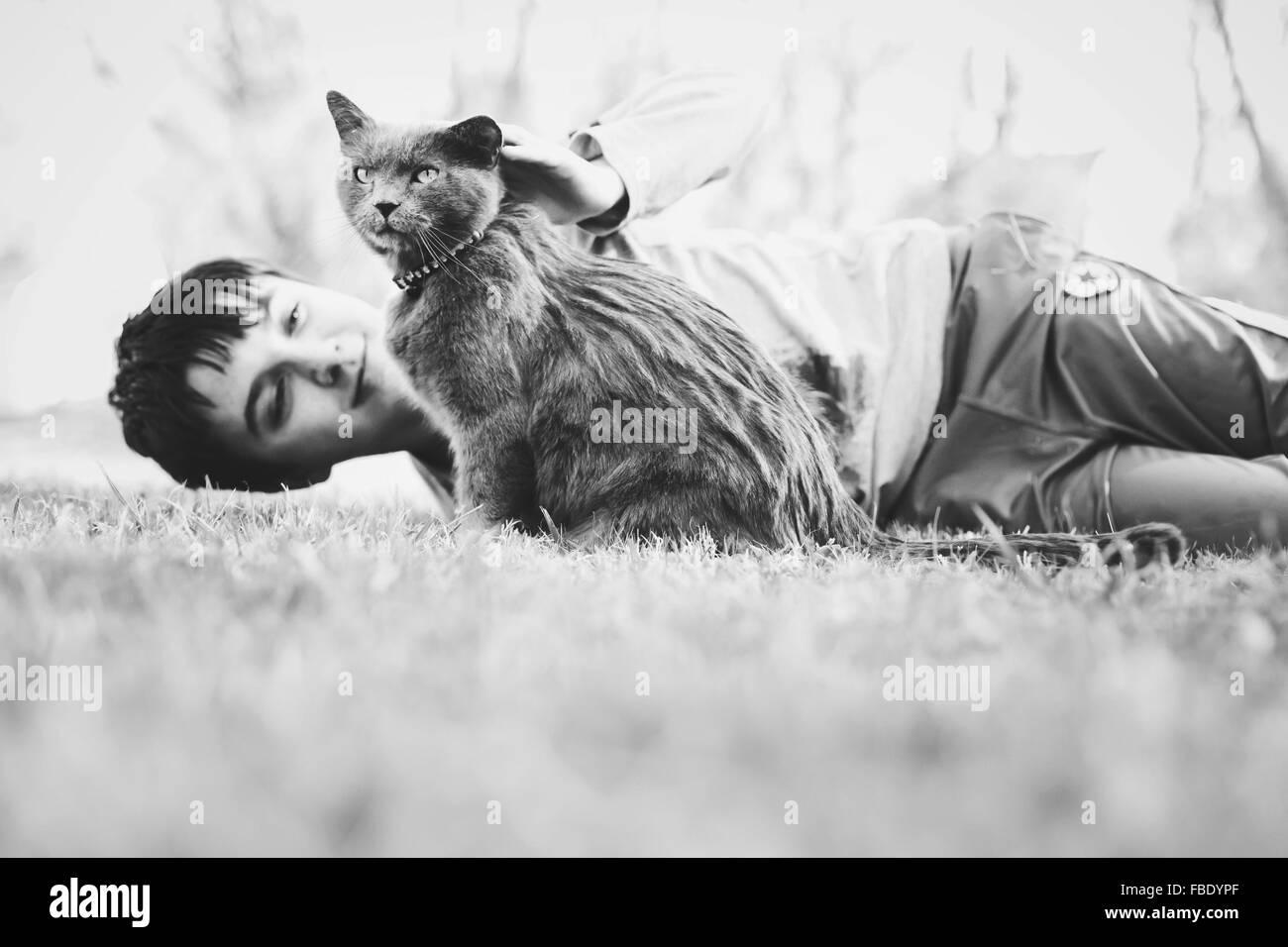 Niño acostado sobre el césped con cat. Imagen De Stock