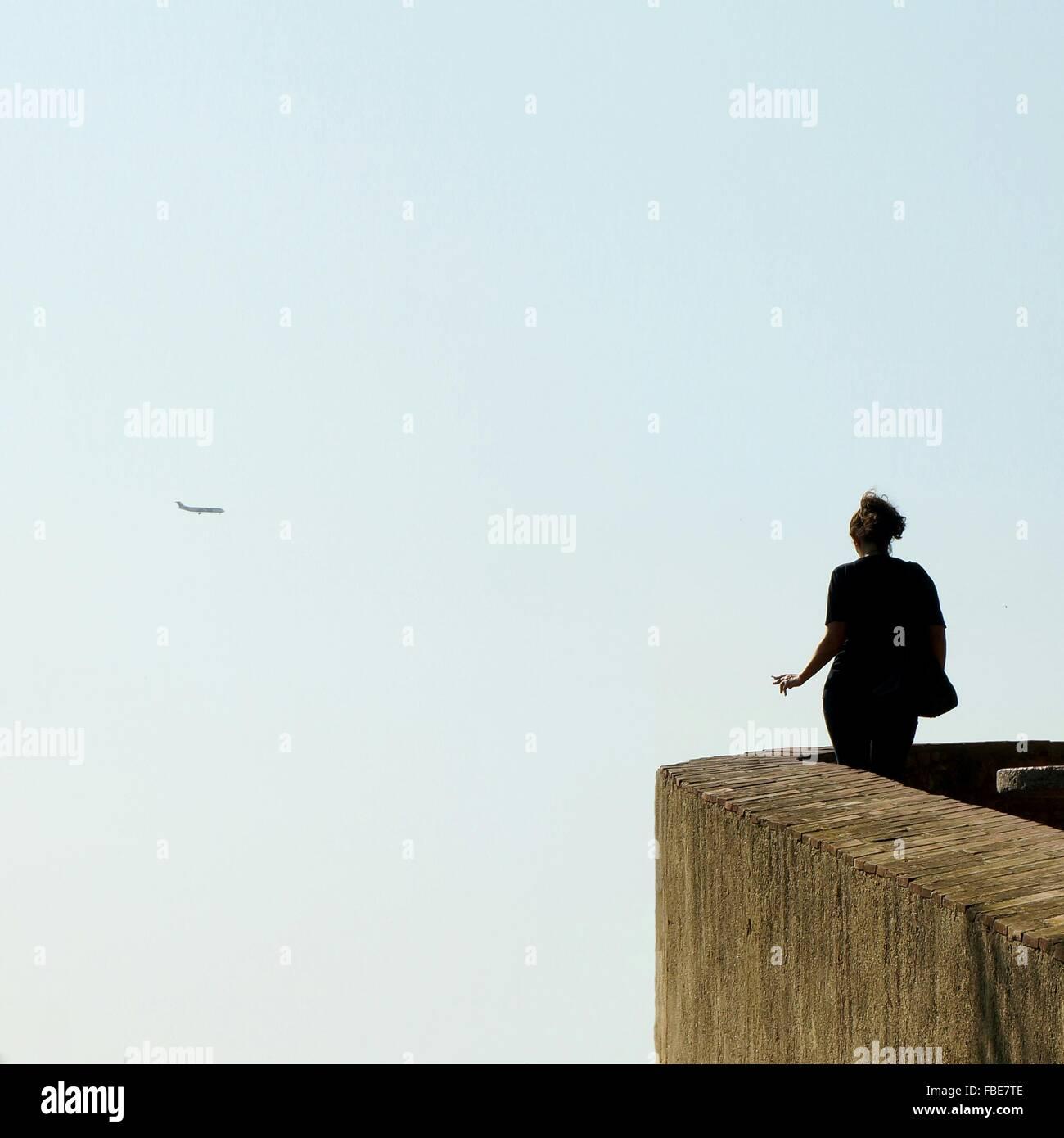 Vista trasera de una mujer mirando avión volando contra el cielo Imagen De Stock
